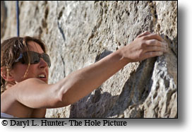Woman Mountain Climber negotatiing tough section of rock wall